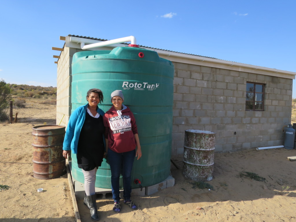 Katriena Fortuin with rainwater harvesting tank to support her family in managing water scarcity in South Africa. Photo by Siya Myeza, Environmental Monitoring Group